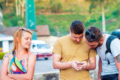 Two young beautiful men are looking at the smartphone screen and a beautiful redheaded girl is looking at them. Royalty Free Stock Image