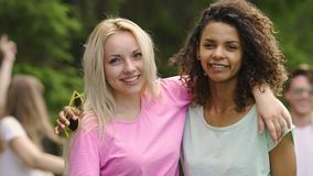 Two young beautiful multiracial women hugging and smiling to camera, friendship. Stock footage stock video footage
