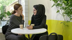 Two young beautiful muslim womans sitting in cafe, one of them in hijab, looking at phone and talking, laughing.  stock video