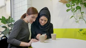Two young beautiful muslim womans sitting in cafe, one of them in hijab, taking selfie and looking at phone, smiling and. Happy stock video footage