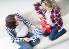 Two young beautiful pregnant women on a sofa Stock Images