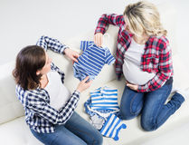 Two young beautiful pregnant women on a sofa Stock Photography