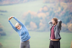 Two young beautiful runners in autumn nature, stretching arms Stock Images