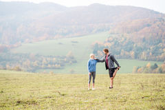 Two young beautiful runners in autumn nature, stretching legs Royalty Free Stock Images