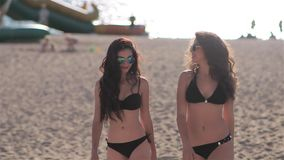 Two young beautiful sexy girl in a bikini walking on the beach. During sunset in slow motion stock video