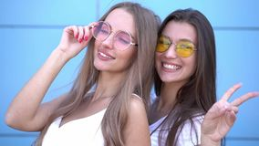 Two young beautiful smiling hipster girls in trendy summer colorful neon sunglasses. Women posing near blue wall. Positive models having fun stock footage