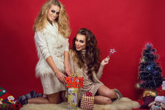 Two young beautiful smiling women in knitted sweaters sitting on the fur near the New Year tree on the bright red background Stock Photography