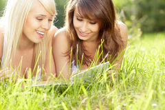 Two young beautiful smiling women reading book Stock Image