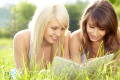Two young beautiful smiling women reading book Stock Photography