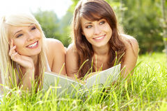Two young beautiful smiling women reading book Royalty Free Stock Image