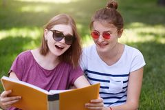 Two young beautiful smiling women reading somethig interesting, sitting on grass at summer green park, prepare for exam toogether royalty free stock photography