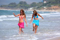 Two young beautiful tanned women walking along sandy beach Stock Photo