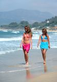 Two young beautiful tanned women walking along sandy beach royalty free stock images