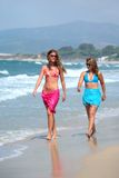Two young beautiful tanned women walking along sandy beach Stock Image