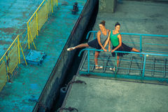 Two young beautiful twin sister dancing ballet in the city with ballet costume. urban sync dance. industrial street dancing. with Royalty Free Stock Images