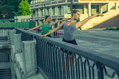Two young beautiful twin sister dancing ballet in the city Stock Photo