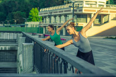 Two young beautiful twin sister dancing ballet in the city Royalty Free Stock Photo