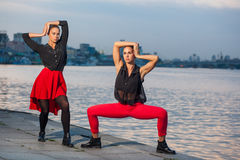 Two young beautiful twin sisters are dancing waacking dance in the city background near river. Stock Photography