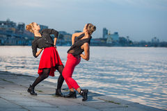 Two young beautiful twin sisters are dancing waacking dance in the city background near river. Stock Image