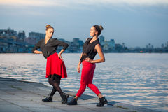 Two young beautiful twin sisters are dancing waacking dance in the city background near river. Stock Photos