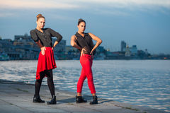 Two young beautiful twin sisters are dancing waacking dance in the city background near river. Stock Images