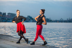 Two young beautiful twin sisters are dancing waacking dance in the city background near river. Royalty Free Stock Photos