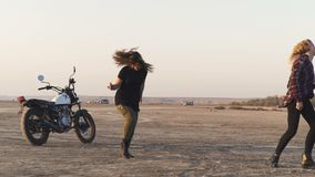 Two young beautiful woman dances in the desert at sunset or sunrise.  Motorcycle on background. Two young beautiful woman dances in the desert at sunset or stock footage