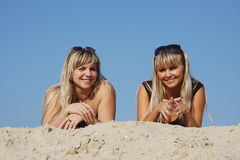 Two young beautiful woman lying on the sand Royalty Free Stock Images