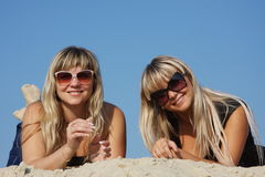 Two young beautiful woman lying on the sand Stock Images