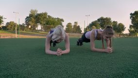 Two young beautiful womans doing plank exercise on soccer field in park during morning, fitness models exercising.  stock video
