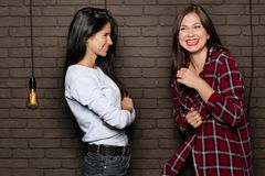 Two young and beautiful womans are posing near the brick wall Stock Image