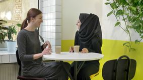 Two young beautiful womans sitting in cafe and laughing, one of them muslim woman in hijab, happy.  stock video footage