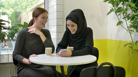 Two young beautiful womans sitting in cafe, one of them muslim woman in hijab, looking at phone and laughing, happy.  stock footage