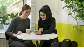 Two young beautiful womans sitting in cafe, one of them muslim woman in hijab, looking at phone, smiling and laughing.  stock video footage