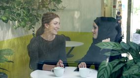 Two young beautiful womans sitting in cafe, one of them muslim woman in hijab, talking and laughing, view from street.  stock video