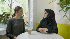 Two young beautiful womans sitting in cafe, one of them muslim woman in hijab telling something to other woman.  stock footage
