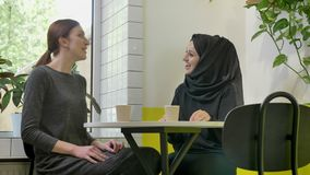 Two young beautiful womans sitting in cafe, one of them pretty muslim woman in hijab, talking and laughing.  stock video