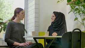 Two young beautiful womans sitting in cafe and talking, one of them pretty muslim woman in hijab, smiling.  stock video footage