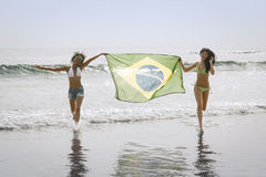 Two young beautiful women in bikini on beach running with Brazil flag. In water Royalty Free Stock Image