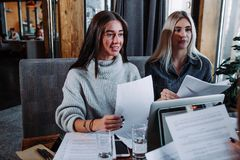 Two young beautiful women at a business meeting in a cafe. Two businesswoman working together about documents, partner discuss plan or idea and opinion meeting Royalty Free Stock Photos
