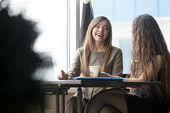 Two young beautiful women chatting in cafe Royalty Free Stock Photos
