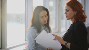 Two Young beautiful women discuss different documents near windows stock footage