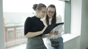 Two Young beautiful women discuss different documents near windows