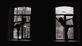Two young beautiful women doing yoga asana on window sill stock video footage