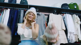 Two young beautiful women having fun in store. Try on hats, laughing, positive emotions stock footage