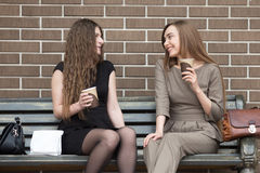 Two young beautiful women holding take away coffee and chatting royalty free stock image