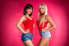 Two young beautiful women posing in Studio in shorts, fitness stock image