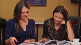 Two young beautiful women read magazines in cafe, smile chat. Stock footage stock video footage