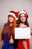 Two young beautiful women in Santa caps standing close with empt. Y sheet of paper in hands. Free space for advertisement or text, mockup for design.New Year Stock Photos