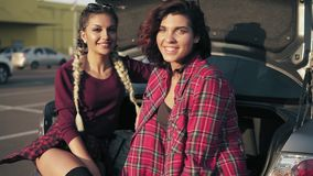 Two young beautiful women sitting in a car trunk in the parking by the shopping mall during sunny day, smiling and stock video